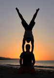 Handstand on the beach. Two men silhouettes at sunset on the beach Stock Images