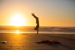 Handstand by the beach Stock Photo