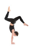 Handstand with bent legs. Sporty young man working out, dance, yoga, pilates, fitness training, doing Bent Legged Stag handstand, side view, full length Royalty Free Stock Photo