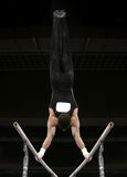 Handstand on parallel bars. Gymnast doing handstand on parallel bars Stock Image