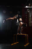 Handstand on the rails. Young woman doing handstand on bars in gym Stock Photography