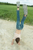 Handstand of teenage boy on dirt road at farm field background outdoors stock photography