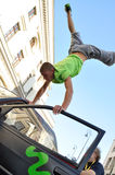 Handstand trick on the top of car. Royalty Free Stock Images