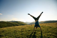 Handstand woman in a sunset mountain top Royalty Free Stock Photos