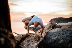 Handstand yoga pose by man on the beach near the ocean Stock Photos