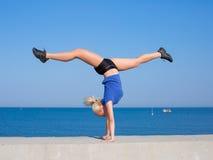 Handstand. Young gymnast on seashore Stock Photos