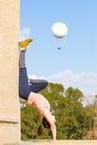 Handstand young woman girl yoga training hot air ballon. Stock Image