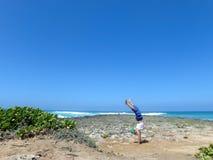 Άτομο Handstanding στους βράχους κοραλλιών στην παραλία ως συντριβή κυμάτων στο θόριο Στοκ Φωτογραφία