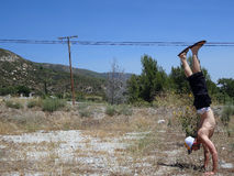 Handstanding in Dirt grass Field in California. With powerlines and Mountain in the background Stock Photography