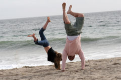 Handstands in the Sand. Father daughter playing on the beach Stock Photos