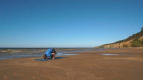 Handstandyogahaltung durch Mann auf dem Strand nahe dem Ozean stock footage