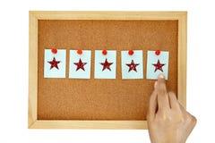 Handstift ein Briefpapier auf Korkenpinnwand mit Stern, Symbol geben fünf des ausgezeichneten Kundendienst-Feedbackkonzeptes, lizenzfreie stockbilder