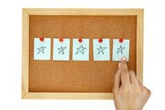 Handstiftbriefpapier auf Korkenpinnwand mit Zeichnung mit fünf Sternen Hand, Symbol geben des ausgezeichneten Kundendienstfeedbac stockbilder