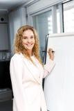 Handstil för affärskvinna på flipdiagram Fotografering för Bildbyråer