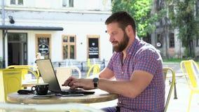 Handstil för den unga mannen på bärbara datorn i kafé, glidare och panna sköt vänstert stock video