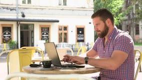 Handstil för den unga mannen på bärbara datorn i kafét, glidare sköt vänstert stock video