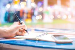 Handstil för hand för kvinna` s på en anteckningsbok med en penna på ett träskrivbord Arkivfoton