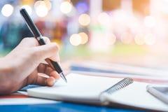 Handstil för hand för kvinna` s på en anteckningsbok med en penna på ett träskrivbord B Royaltyfria Foton