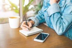 Handstil för hand för kvinna` s på en notepad med en penna Arkivfoto