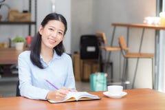 Handstil för ung kvinna för härlig affär asiatisk på anteckningsboken på tabellen, flickaarbete på coffee shop Royaltyfri Fotografi