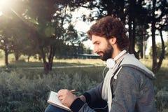Handstil för ung man i anteckningsbok på naturen, sidosikt Royaltyfri Bild