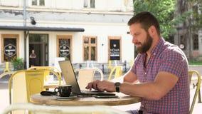 Handstil för ung man på bärbara datorn i kafé lager videofilmer