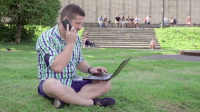 Handstil för ung man på bärbara datorn, svarspåringning, sammanträde på gräs stock video