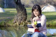 Handstil och läsning för ung kvinna som en bok i en höst parkerar Royaltyfri Bild