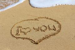 Handstilen på sand, älskar jag dig Oceaniskt skum royaltyfri foto