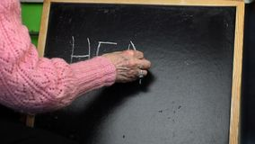 Handstilord HÄLSA för gammal kvinna på svart tavla arkivfilmer