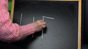 Handstilord LIV för gammal kvinna på svart tavla arkivfilmer
