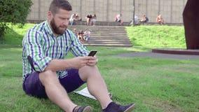 Handstilsms för ung man på smartphonen, sammanträde på gräs steadicam lager videofilmer