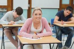 Handstilstudenter i ett klassrum Arkivbild