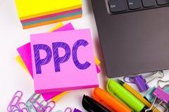 Handstiltext som visar PPC - lön per klicken som göras i kontoret med omgivning liksom bärbara datorn, markör, penna Affärsidé fö royaltyfria bilder
