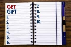 Handstiltextvisningen får gåvan Affärsidé för den fria Shoping kupongen som är skriftlig på anteckningsbokanmärkningspapper, träb Arkivbild