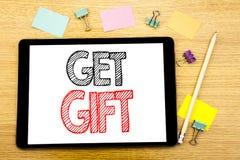 Handstiltextvisningen får gåvan Affärsidé för den fria Shoping kupongen som är skriftlig på minnestavlabärbara datorn, träbakgrun Fotografering för Bildbyråer