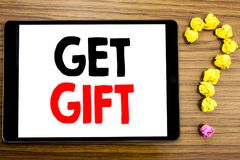 Handstiltextvisningen får gåvan Affärsidé för den fria Shoping kupongen som är skriftlig på minnestavladatoren på träbakgrunden m Arkivfoton