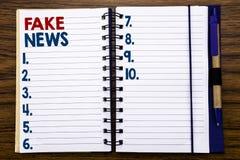 Handstiltextvisningen fejkar nyheterna Affärsidé för Hoax journalistik som är skriftlig på anteckningsbokanmärkningspapper, träba arkivbild