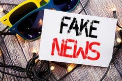Handstiltextvisningen fejkar nyheterna Affärsidé för Hoax journalistik som är skriftlig på klibbig anmärkning med kopieringsutrym arkivfoton