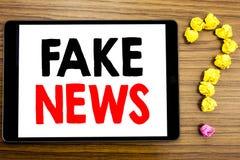 Handstiltextvisningen fejkar nyheterna Affärsidé för Hoax journalistik som är skriftlig på minnestavladatoren på träbakgrunden me arkivfoto