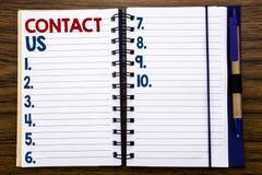 Handstiltextvisningen kontaktar oss Affärsidé för kundservice som är skriftlig på anteckningsbokanmärkningspapper, träbakgrund me arkivfoton