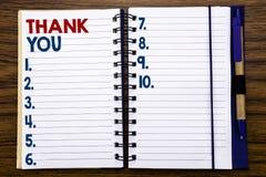 Handstiltextvisningen tackar dig Affärsidéen för tacksamhet tackar skriftligt på anteckningsbokanmärkningspapper, träbakgrund med Arkivbild