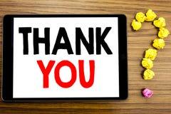 Handstiltextvisningen tackar dig Affärsidéen för tacksamhet tackar skriftligt på minnestavladatoren på träbakgrunden med que Royaltyfri Bild