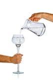 Handströmendes Wasser vom Glaskrug Stockfotos