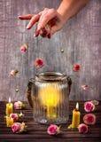 Handstreuung Rosebuds über den Kerzen Lizenzfreies Stockfoto