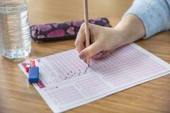 Handstudent het testen in oefening en het nemen vullen de computerblad van het examencarbonpapier met potlood in bij de ruimte va stock foto