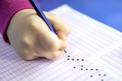 Handstudent het testen in oefening en het nemen vullen de computerblad van het examencarbonpapier met potlood in bij de ruimte va stock afbeeldingen