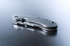Handtag av den liggande militära kniven för A som ligger på mörker som malas med reflexion Fotografering för Bildbyråer