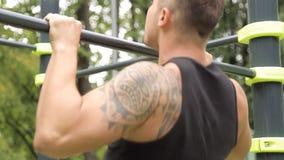 Handtag för den unga mannen ups stånggenomkörareövning lager videofilmer