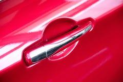 Handtag på röda bils dörr fotografering för bildbyråer